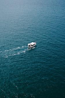 小さな観光船がヘリコプターから水テクスチャ空中フレームに浮かぶ