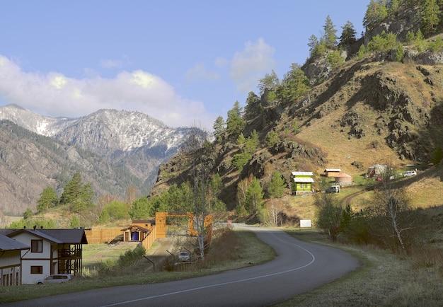 Небольшие туристические домики на склонах гор, покрытые соснами и камнями.