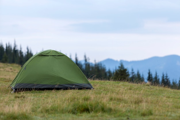 Small tourist tent on grassy mountain hill. summer camping in mountains at dawn. tourism .