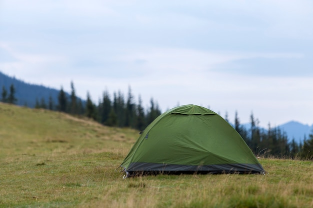 Small tourist tent on grassy mountain hill