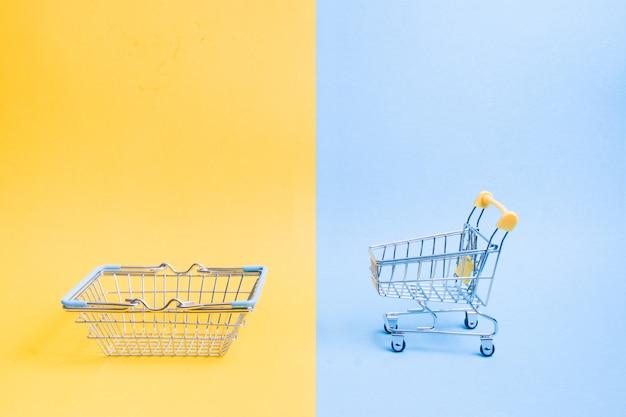 파란색과 노란색 배경, 복사 공간, 쇼핑 개념에 작은 장난감 바구니와 쇼핑 트롤리