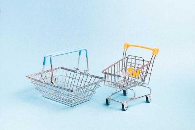 작은 장난감 바구니와 파란색 배경에 쇼핑 트롤리, 복사 공간, 쇼핑 개념