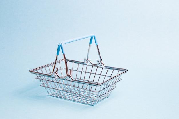 밝은 파란색 배경, 복사 공간, 쇼핑 개념에 작은 장난감 바구니