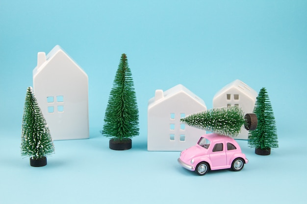 Small toy car carring christmas tree over the roof. sesonal holidays, greeting card