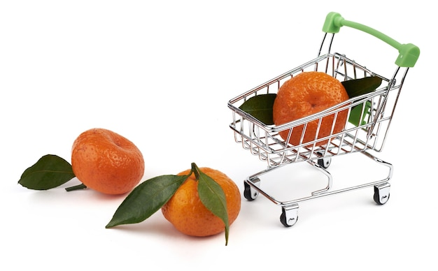 슈퍼마켓의 식료품을 위한 작은 장난감 카트와 흰색 배경에 분리된 녹색 잎이 있는 3개의 귤.