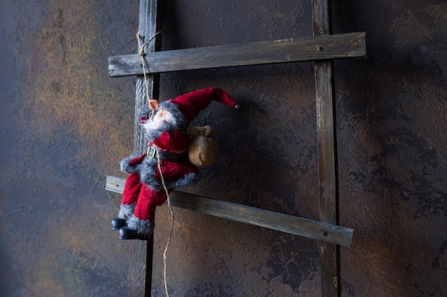 Small toy in the form of santa claus on a wooden ladder