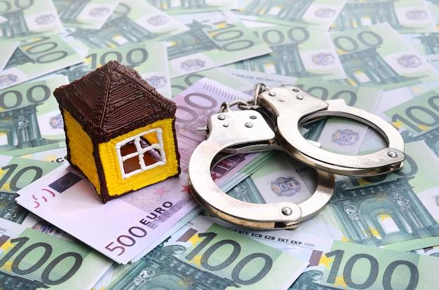 Маленький игрушечный домик и наручники лежат на множестве зеленых денежных номиналов по 100 евро