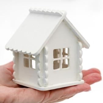 Маленький игрушечный домик в руке