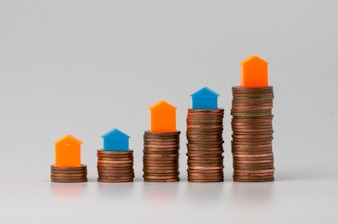 Small toy house on stacked of bronze coins isolated on white background.