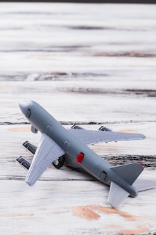 Small toy passanger plane on white wood. close up grey airplane is turned to the left.