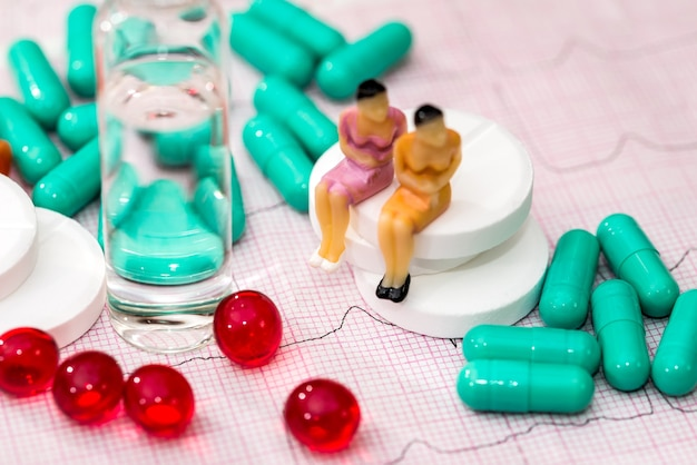 작은 장난감 사람들은 알약 중 심전도에 있습니다.