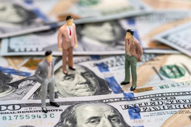 달러 지폐에 작은 장난감 사람들