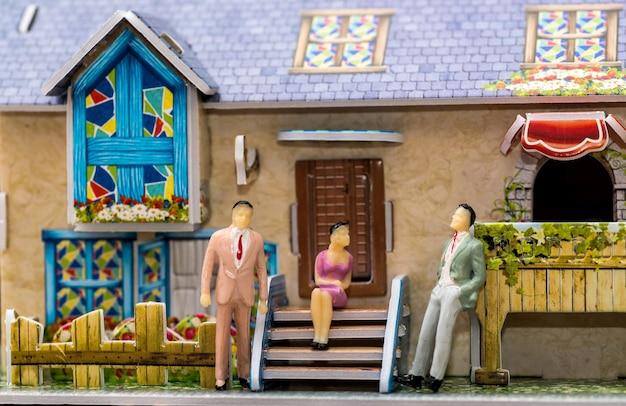 小さなおもちゃの人がおもちゃの家の向かいに立っています