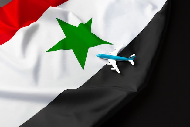 Small toy plane over the fabric flag of syria
