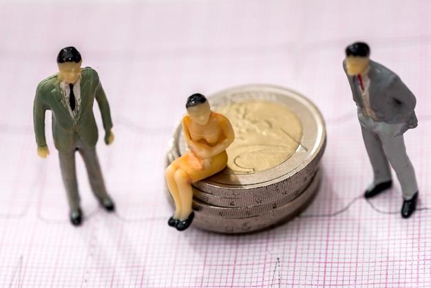 작은 장난감 사람들은 유로 동전과 제품에 있습니다.