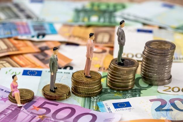 小さなおもちゃの人々はユーロ硬貨とユーロ紙幣にあります