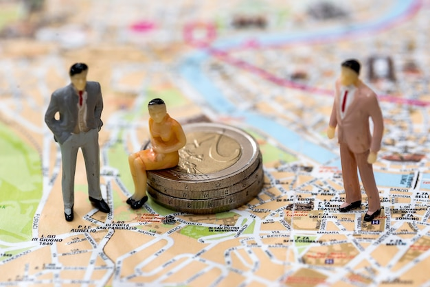 작은 장난감 사람들은 유로 동전과지도에 있습니다.