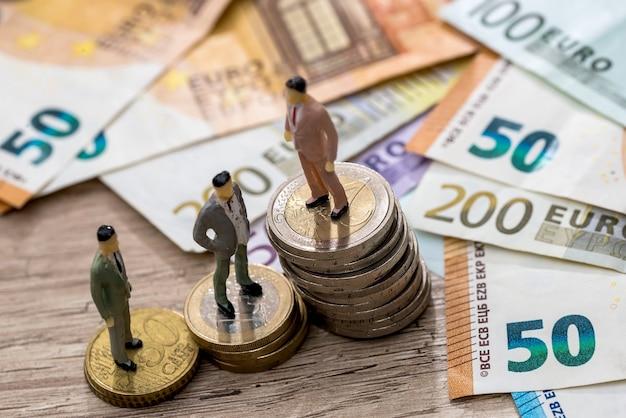 人々がユーロ硬貨やユーロに近いところにある小さなおもちゃ
