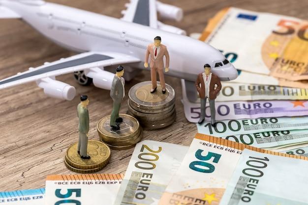 人々がユーロや飛行機の近くのユーロ硬貨で見つける小さなおもちゃ