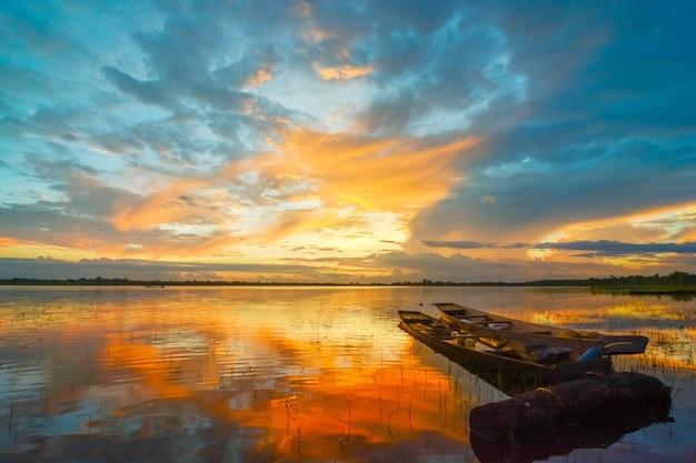 日没時に川沿いに静かに停泊する小さな伝統的なタイの漁船。