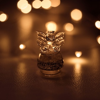 A small transparent angel holds a star on a dark brown background with bright lights bokeh.
