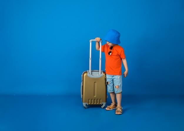 가방을 가진 작은 여행자는 텍스트를위한 공간이있는 파란색 벽에 선다.