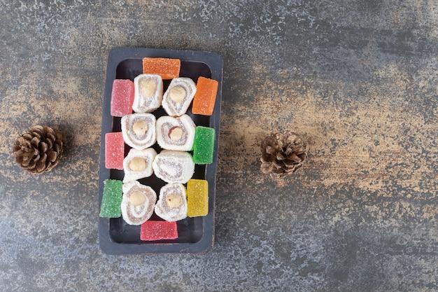 Небольшой поднос с мармеладом и рахат-лукумом рядом с рождественскими украшениями на деревянной поверхности