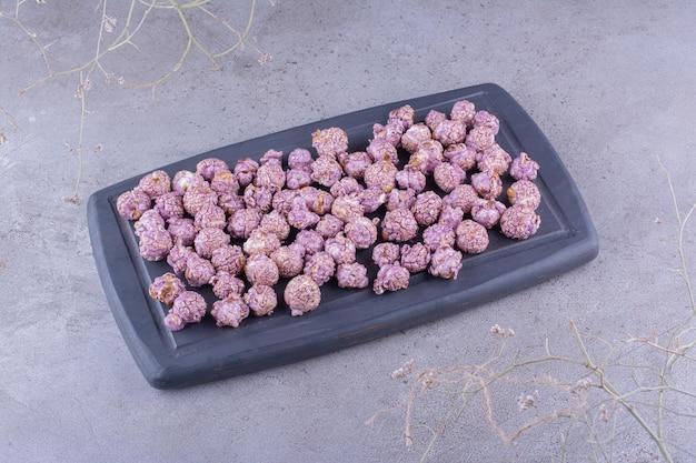 Небольшой поднос с фиолетовым попкорном, покрытым конфетами, на мраморном фоне. фото высокого качества