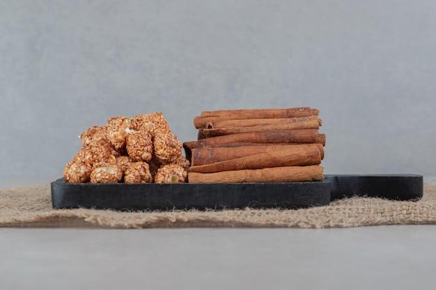 Небольшой поднос со стопками конфет попкорна и кусочками корицы на мраморном столе.