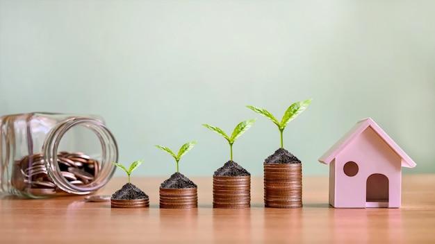 부동산 투자와 모기지를 시뮬레이션하는 주택 모델과 동전 더미에서 자라는 작은 나무