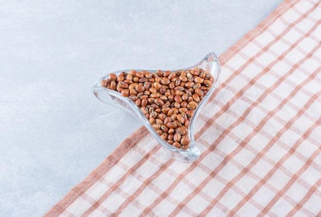 Piccolo piatto snack triangolare pieno di fagioli rossi su tovaglia, su superficie di marmo
