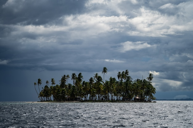 Small tropical island with coconut palm trees during stormy cloudy weathre adventure and travel concept