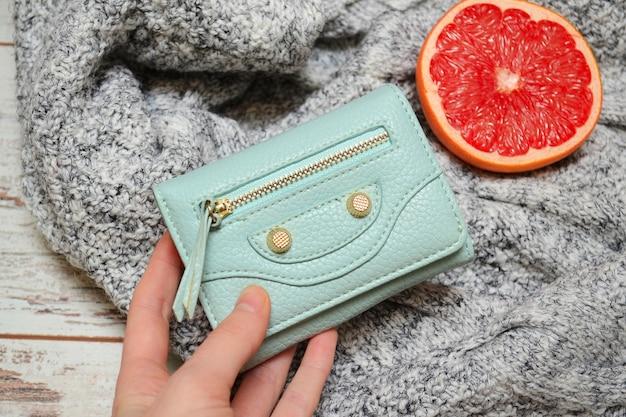 セーターの背景に女性の手で小さなターコイズブルーの財布