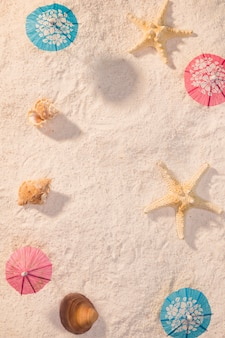 Small umbrellas with shells on beach