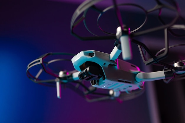 The small unmanned aerial vehicle with the protection of the propeller blades in flight on a neon background inside the room
