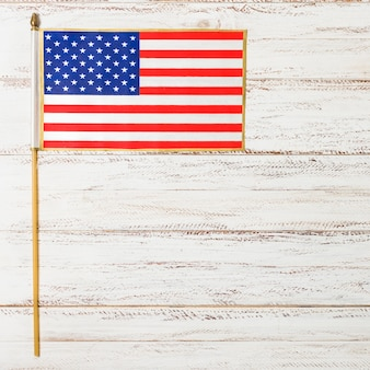 Small usa flag for independence day on white wooden desk
