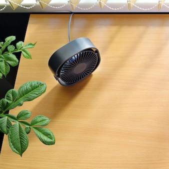 Маленький usb-вентилятор на столе при мягком освещении