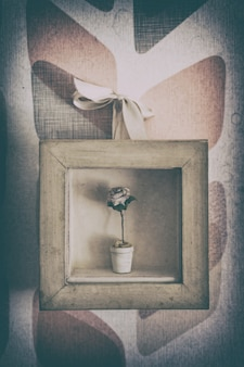 Small vase with rose inside a small picture frame.