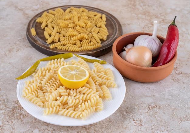 Небольшая миска для овощей и порции пасты в сыром и приготовленном состоянии на мраморной поверхности.