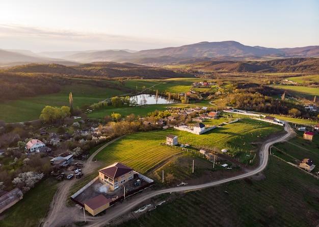 緑の野原と丘に囲まれた小さな村。田園生活。鳥瞰図。