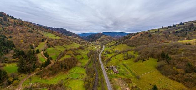 道路沿いのウクライナの秋の日にカルパティア山脈の山の谷にある小さな村