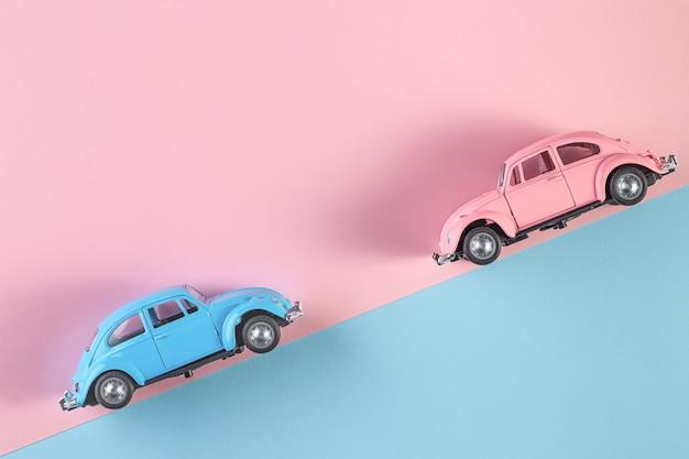 ピンクと青の壁に小さなヴィンテージのレトロなおもちゃの車。レーストラックのレーシングカー。自動車と交通機関のシンボル。テキスト用のスペースをコピーする