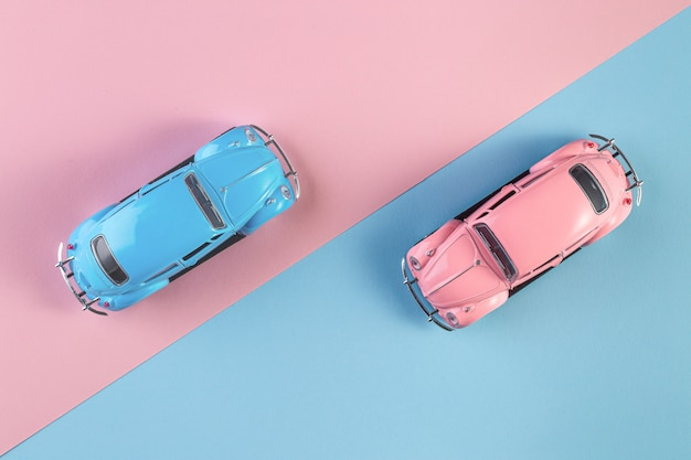 Small vintage retro toy cars on a pink and blue background