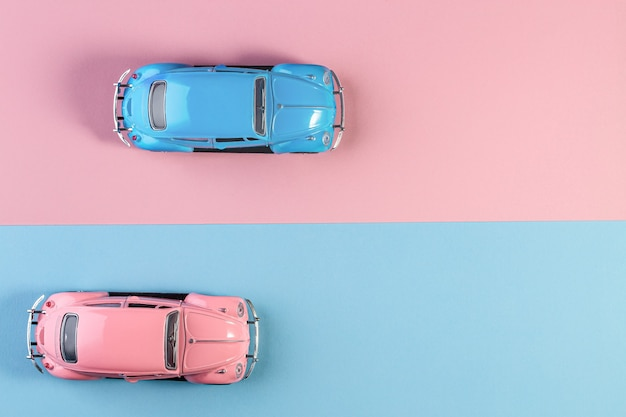 Small vintage retro toy cars on a pink and blue surface