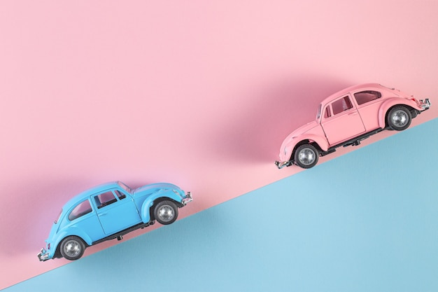 Small vintage retro toy cars on a pink and blue wall. racing cars on the race track. automobile and transportation symbol. copy space for text