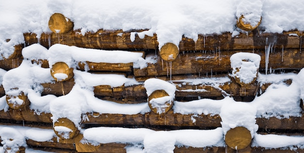 A small wall of small logs background under snow at winter