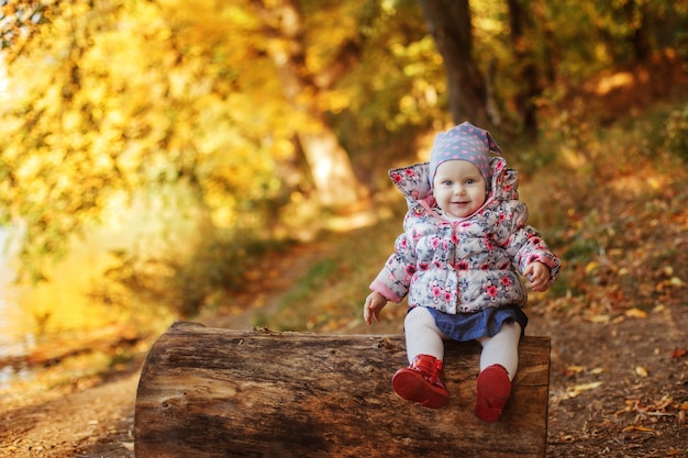 A small warmly dressed girl sits on a log in the park in autumn