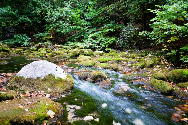 Small waterfall and green clear still water lagoon surrounded by green grass hills on summer day