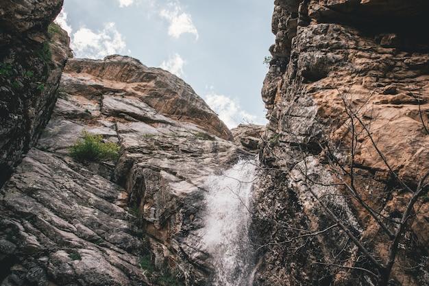 Небольшой водопад в скалистых горах снят снизу