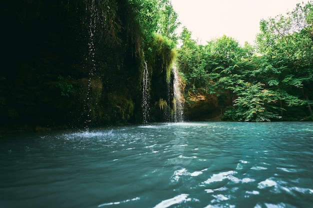 A small waterfall and a lake surrounded by trees in the summer. wonderful landscape at the mouth of the river.